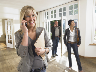 female real estate agent on phone in show house clients behind.
